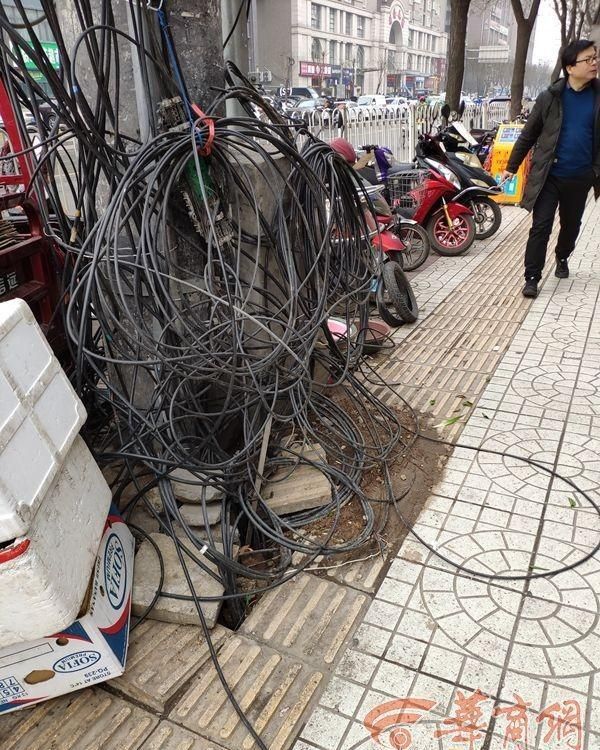 西安雁塔区青松路乱象:地面坑洼、线缆下垂、车辆占道……