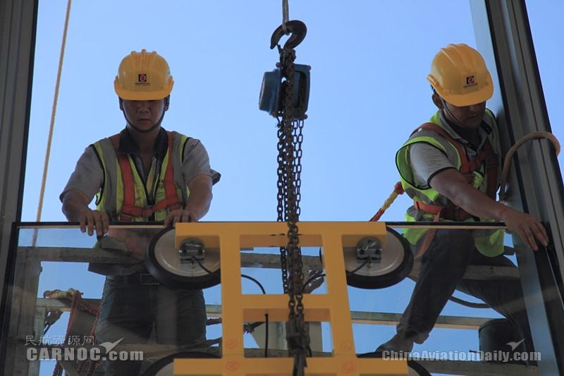 图:工人将玻璃嵌入航站楼钢结构框架内