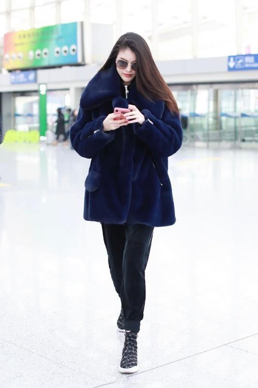 何穗穿深蓝色羊羔大衣,还好配了运动裤和运动鞋,不会显老气