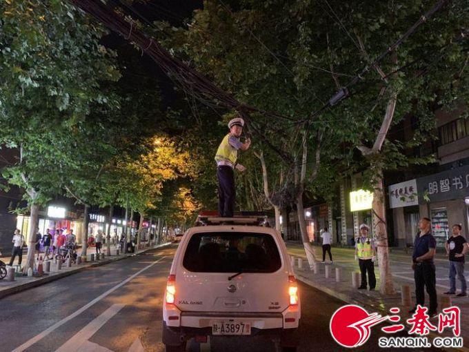 深夜线缆垂落存在安全隐患     交警站到警车顶上托举固定