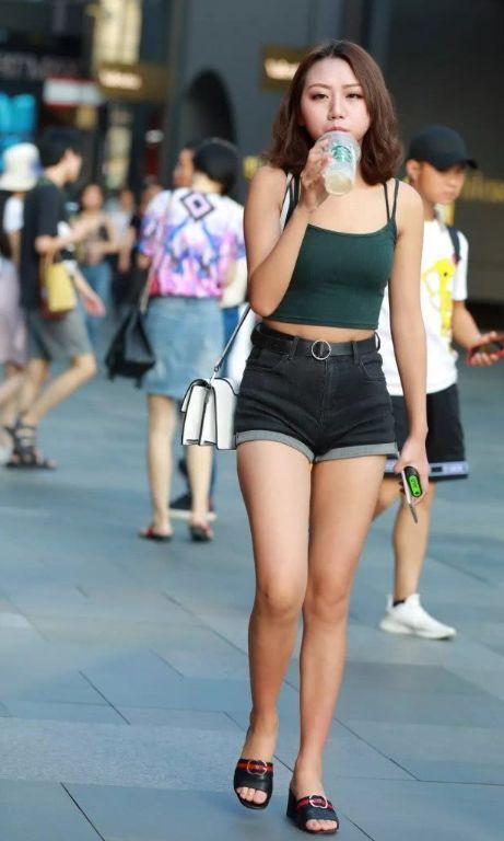 美女牛仔短裤搭配吊带,喝着冰冻奶茶,十分潇洒