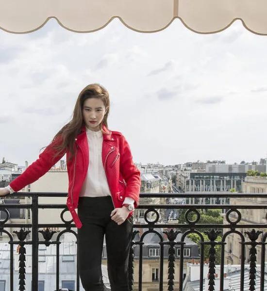 刘亦菲穿红色夹克,身后可以清晰地看见埃菲尔铁塔,女神范儿十足