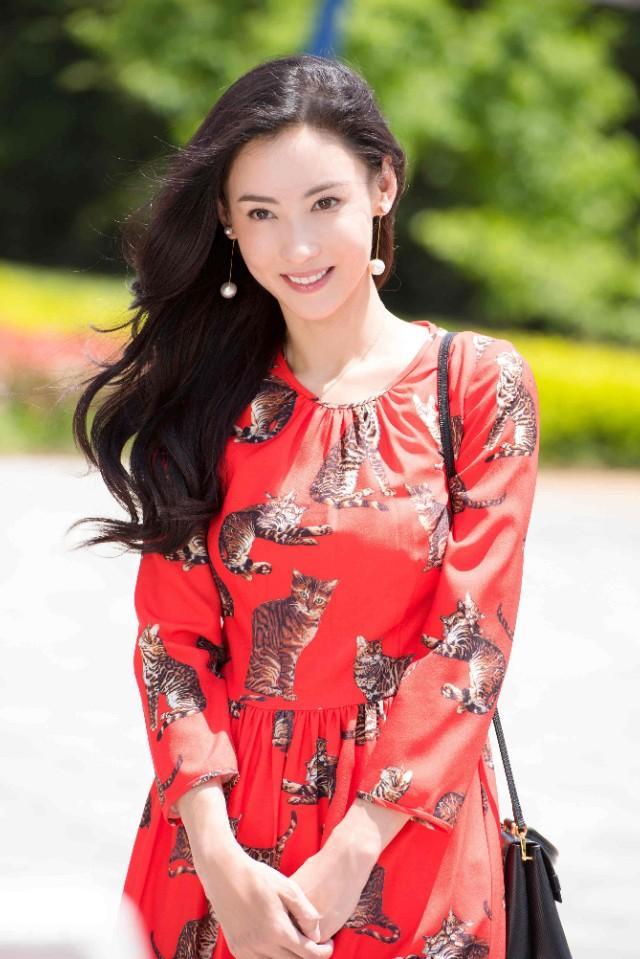 张柏芝穿红色印猫连衣裙现身,阳光下戴珍珠耳环