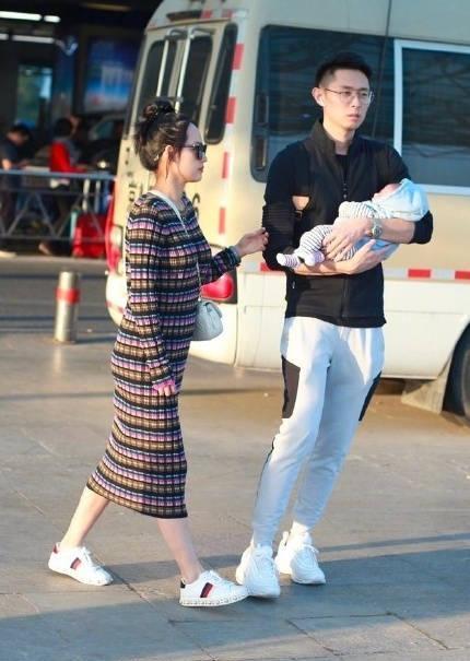 张嘉倪针织裙配丸子头少女搭配走机场,富二代老公抱孩子又帅又潮