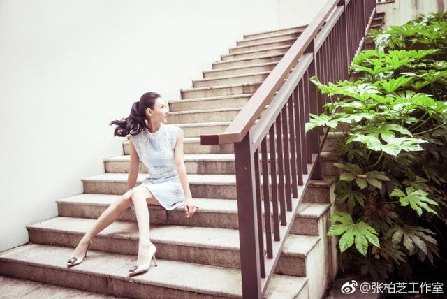 张柏芝穿粉蓝连衣裙搭白色呢西装,坐立在楼梯上