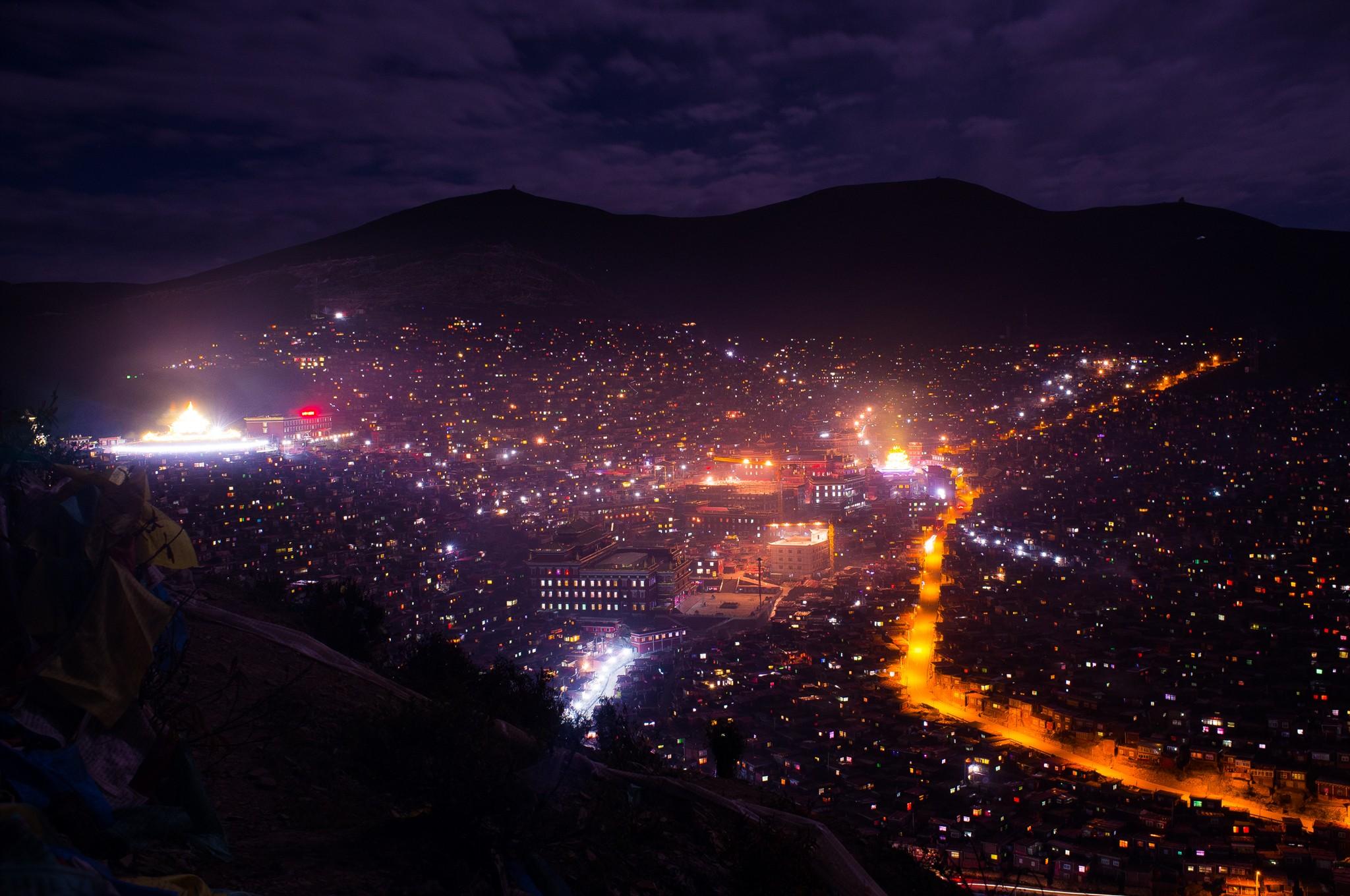 四川一处山坡上密密麻麻数万座僧房,灯光亮起,就像天上的星星
