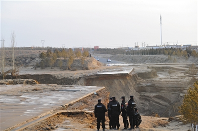 1月7日,宁夏灵武市,洪水将灵武市东沿山处的下白路冲毁,冲开一道几十米宽近十米深的豁口。图/视觉中国