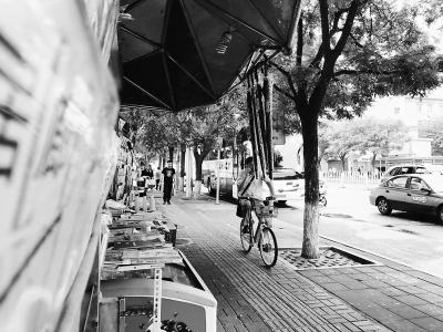 5月17日12时许,崇文门地铁站北侧路东一小商亭下,商亭主人为招徕生意挂出4把雨伞,不少过往行人被磕碰。李小琴 图/文