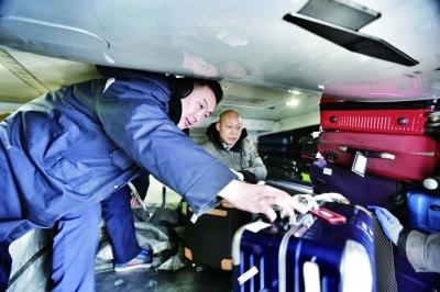 飞机的货舱狭小,高度仅有1米左右,李家鹏左须半蹲着装卸行李摄/记者 柴程